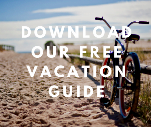 "Beach view with a bike with overlaying text saying ""download our free Vacation Guide"""