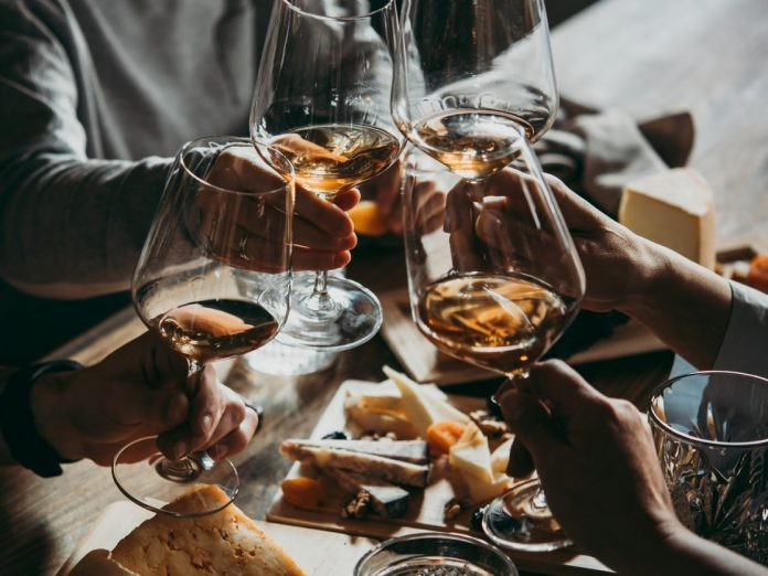 Friends toasting with glasses of wine and eating cheese |Chatham Wine Bar